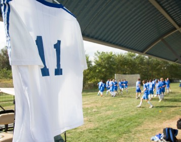 Former Trailblazer Blake Snyder's jersey hangs in the foreground as the men's soccer team warms up for a memorial game, their last home game of the 2016 season. Snyder, a St. Louis County Police Officer, was killed in the line of duty in October 2016.